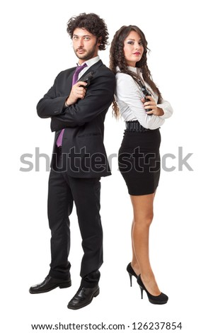A businessman and a businesswoman (or maybe a couple of spies or gangster) holding guns over a white background - stock photo