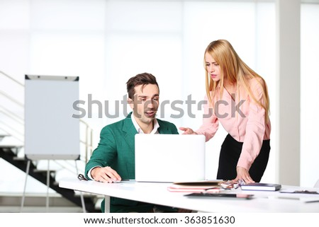 A businessman and businesswoman working in a conference room