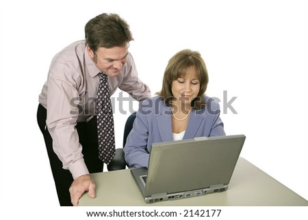 A businessman and woman working together using a laptop.  Isolated on white.