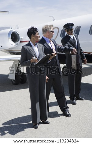 A businessman, businesswoman and airline pilot in front of private jet - stock photo