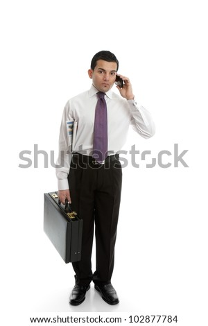 A businessman carrying a black briefcase and using a mobile cell phone. - stock photo