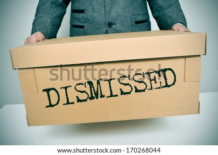 a businessman carrying a box with the word dismissed written in it - stock photo