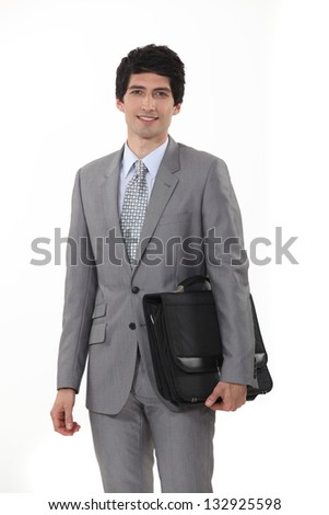 A businessman carrying his briefcase. - stock photo