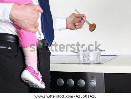 A Businessman cooking with Baby on arm - stock photo