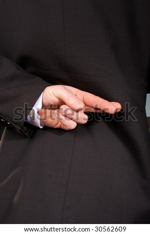 a businessman crosses his fingers behind his back