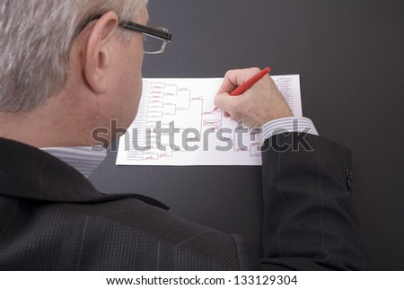 A businessman crossing out teams on his busted March Madness bracket - stock photo
