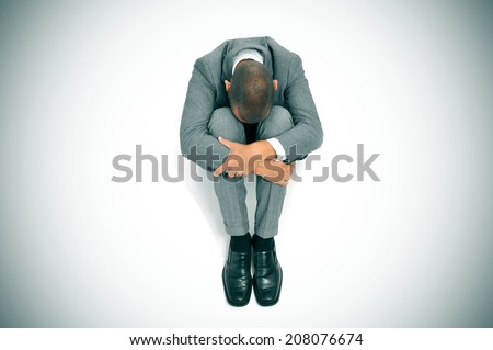 a businessman curled up in the floor with his head between his knees - stock photo