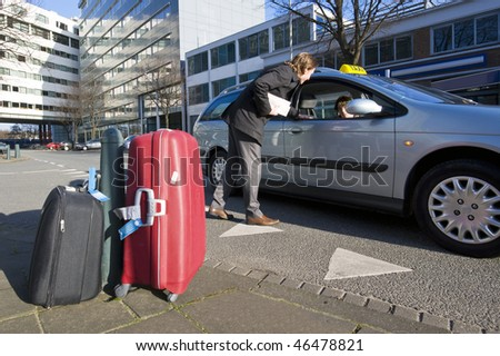 A businessman discussing his fare with a taxi driver - stock photo