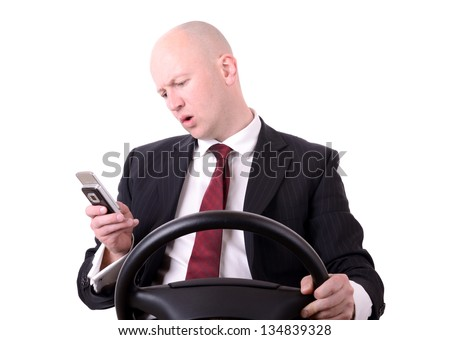 a businessman distracted by mobile phone when driving isolated on white - stock photo
