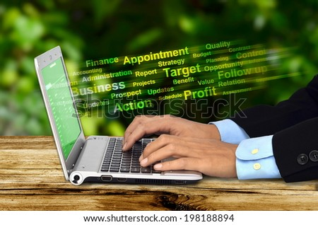 A businessman doing his job with  an internet connected laptop with a green background. Can be use for work from home concept - stock photo