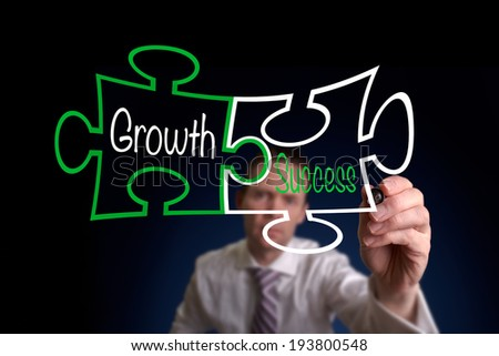 A Businessman drawing a growth success puzzle concept. - stock photo