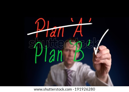 A businessman drawing a Plan A and Plan B concept on a glass screen. - stock photo