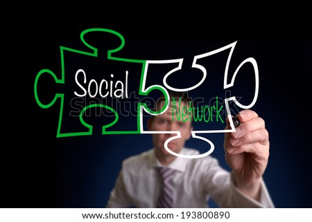 A Businessman drawing a social network puzzle concept. - stock photo