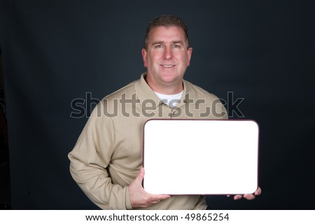 A businessman dresses in business casual clothing displays a blank whiteboard.  Whiteboard is blank to allow designers to place copy.