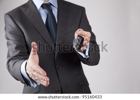 A businessman extending car key and holding out his hand to shake, isolated on greybackground