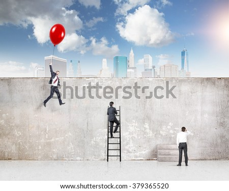 A businessman flying a red balloon, a businessman climbing a ladder and one standing at a concrete wall separating them from New York, blue sky above. Concept of reaching aim. - stock photo