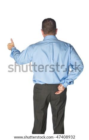 A businessman gives a thumbs up and has his fingers crossed behind his back as if lying or deceiving his clients. - stock photo