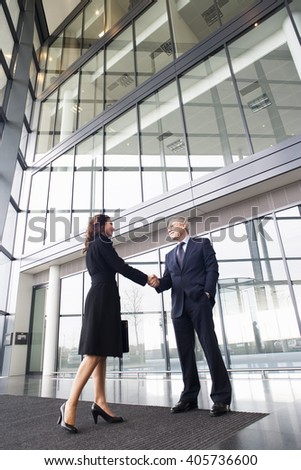 A businessman greeting a female client - stock photo
