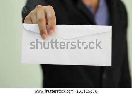 A businessman handing in a blank envelope  (focus on hand holding envelope, other out of focus)