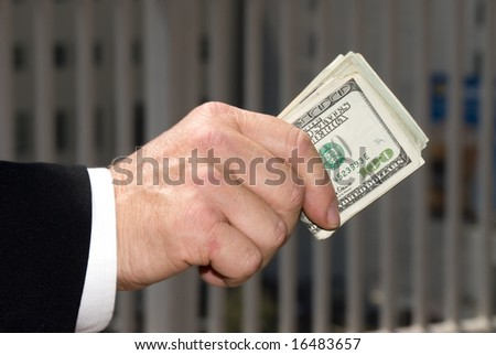 A businessman handing over a wad of cash. - stock photo