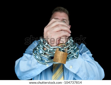 A businessman has his hands chained up to insinuate that he needs to be controlled. - stock photo