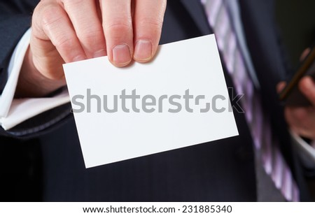 A businessman holding a blank business card - stock photo