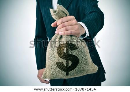 a businessman holding a burlap money bag - stock photo