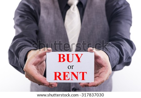 A businessman holding a business card with the words, buy or rent, written on it.  - stock photo