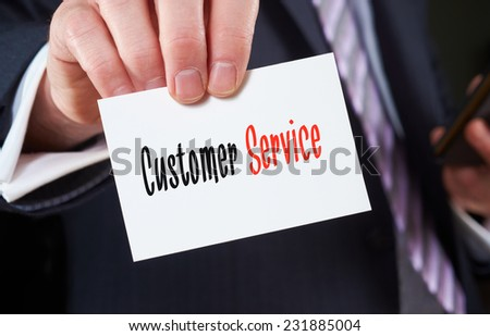 A businessman holding a business card with the words,  Customer Service, written on it. - stock photo