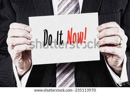A businessman holding a business card with the words,  Do It Now, written on it. - stock photo