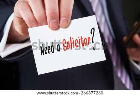 A businessman holding a business card with the words, Need a Solicitor, written on it. - stock photo