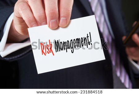 A businessman holding a business card with the words, Risk Management, written on it. - stock photo