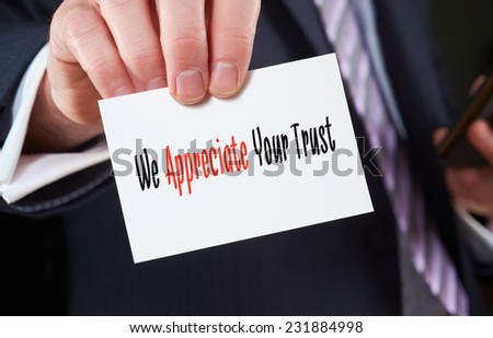 A businessman holding a business card with the words,  We Appreciate Your Trust, written on it. - stock photo