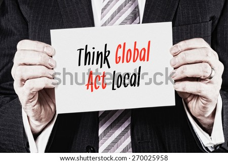 A businessman holding a card with the words, Think Global Act Local, written on it. - stock photo