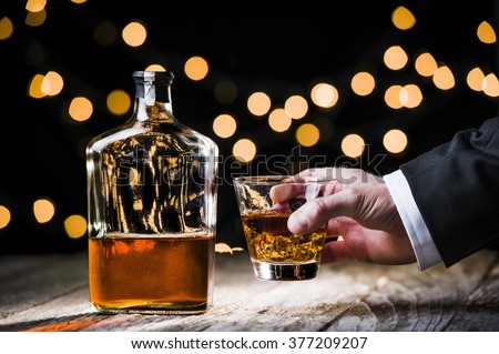a businessman holding a glass of whiskey.