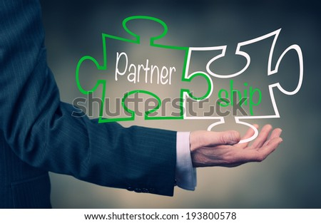 A businessman holding a Partnership Puzzle Concept. - stock photo