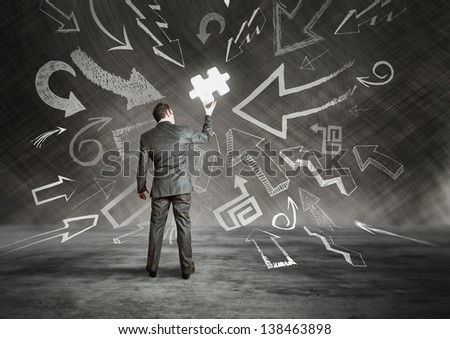 A businessman holding a puzzle piece, with pointing arrows. - stock photo