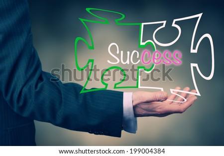 A Businessman holding a success puzzle concept. - stock photo