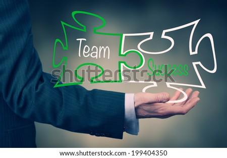 A Businessman holding a Teamwork puzzle concept. Instagram Style Filter Applied. - stock photo