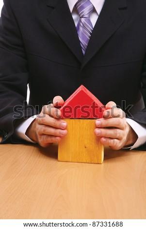 A businessman holding a toy house, real estate presentation, closeup - stock photo