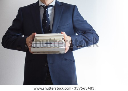 A businessman holding books