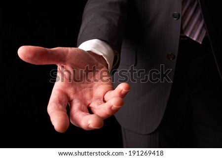 A businessman holding out his hand to shake the hand of another.