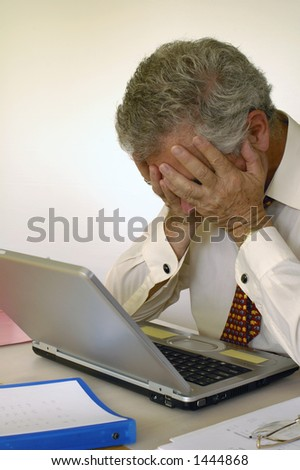 A businessman holds his head in his hands in front of his laptop computer, in despair. Space for text on the white background.