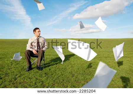 A businessman in a field sat with his paperwork flying around him. - stock photo