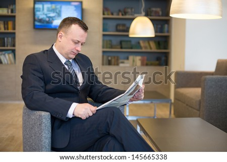 A businessman in a suit and tie sitting on a chair and reading a newspaper