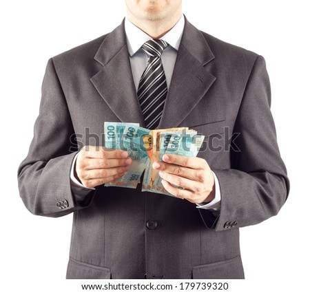 A businessman in a suit counting brazilian money