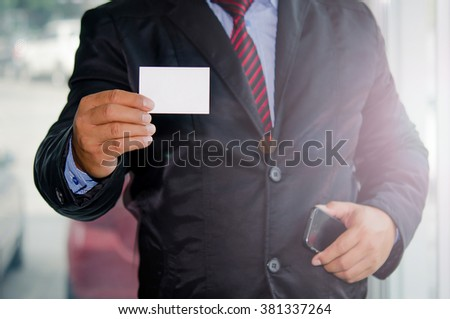 a businessman in a suit holding a piece of paper. - stock photo