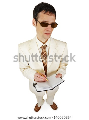 A businessman in a white suit with a notebook - stock photo