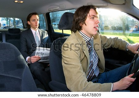 A businessman in the backseat of a taxi - stock photo