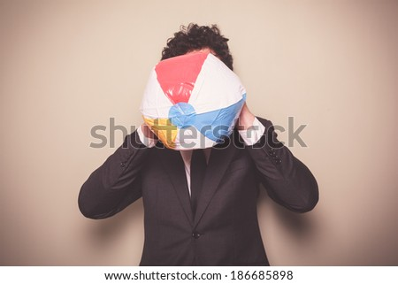 A businessman is blowing up a multi colored beach ball - stock photo